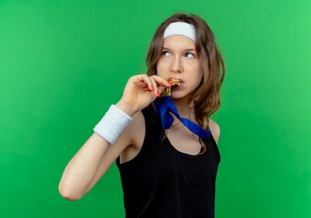 Młoda dziewczyna fitness w czarnej odzieży sportowej z opaską i złotym medalem na szyi, patrząc na bok, gryząc swój medal, stojąc na zielonej ścianie