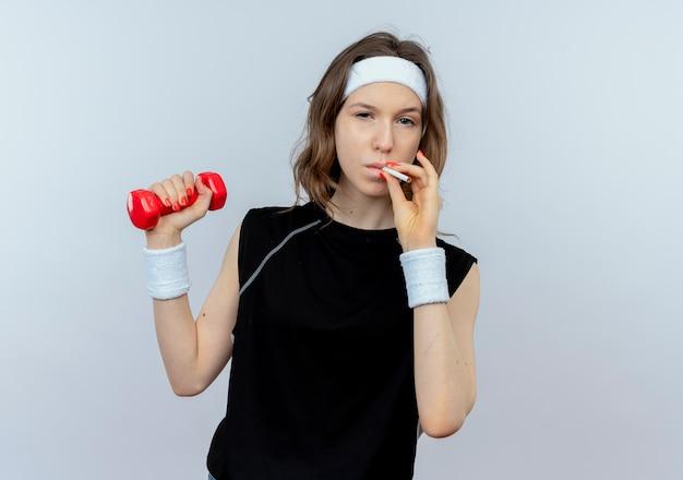Młoda dziewczyna fitness w czarnej odzieży sportowej z pałąkiem na głowę, ćwicząc z hantlami i paleniem papierosów koncepcja złego nawyku, stojąc na białej ścianie