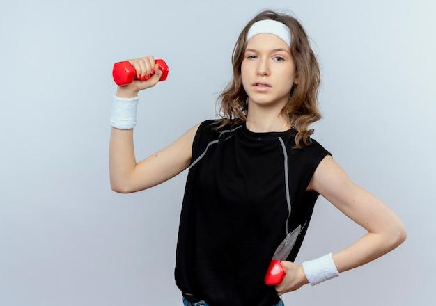 Młoda dziewczyna fitness w czarnej odzieży sportowej z pałąkiem na głowę, ćwicząc z hantlami, patrząc pewnie stojąc na białej ścianie