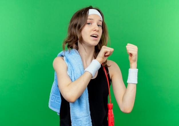 Młoda dziewczyna fitness w czarnej odzieży sportowej z pałąkiem na głowę i ręcznikiem na ramieniu uśmiechnięty, wskazując na zielono
