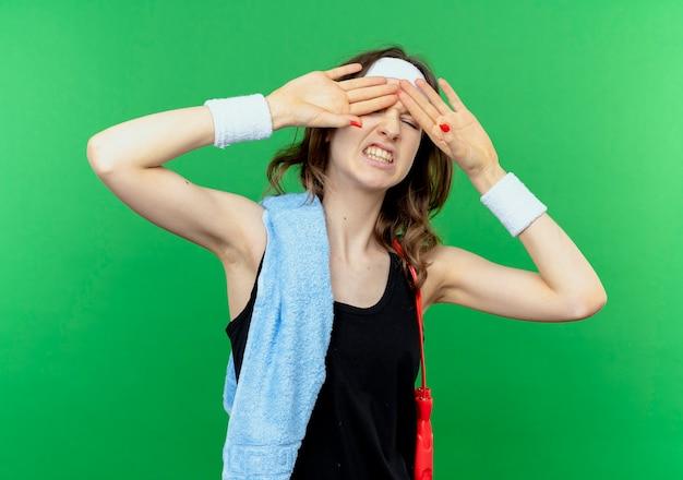 Młoda dziewczyna fitness w czarnej odzieży sportowej z pałąkiem na głowę i ręcznikiem na ramieniu zakrywającym oczy z zirytowanym wyrazem stojącym nad zieloną ścianą