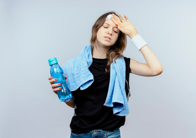 Młoda dziewczyna fitness w czarnej odzieży sportowej z pałąkiem na głowę i ręcznikiem wokół szyi, trzymając butelkę wody wyglądający na zmęczonego stojącego na białej ścianie