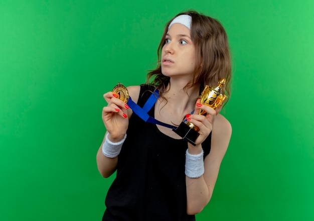Młoda dziewczyna fitness w czarnej odzieży sportowej z pałąkiem na głowę i złotym medalem na szyi, trzymając trofeum na boku, zmartwiona zielenią