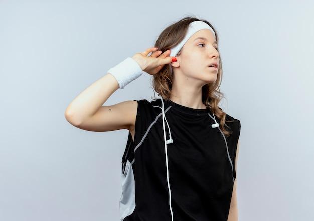Młoda dziewczyna fitness w czarnej odzieży sportowej z pałąkiem na głowę, patrząc na bok, dotykając jej ucha, próbując słuchać stojąc na białej ścianie