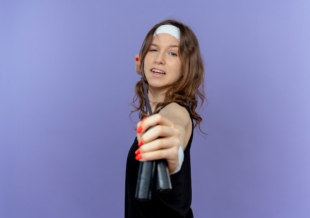 Młoda dziewczyna fitness w czarnej odzieży sportowej z pałąkiem na głowę trzyma skakankę jak celowanie ze strzałką i łukiem stojącym nad niebieską ścianą