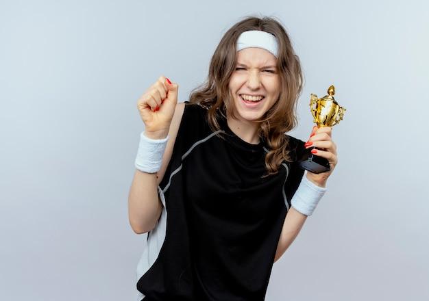Młoda dziewczyna fitness w czarnej odzieży sportowej z pałąkiem na głowę trzyma trofeum zaciskając pięść szczęśliwy i podekscytowany stojąc nad białą ścianą