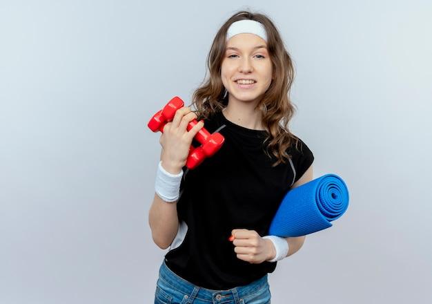 Młoda dziewczyna fitness w czarnej odzieży sportowej z pałąkiem na głowę, trzymając hantle i matę do jogi, patrząc pewnie stojąc na białej ścianie