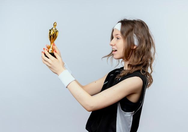 Młoda dziewczyna fitness w czarnej odzieży sportowej z pałąkiem na głowę trzymając trofeum patrząc na to szczęśliwa i podekscytowana stojąc na białej ścianie