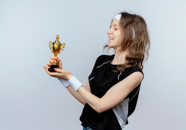 Młoda dziewczyna fitness w czarnej odzieży sportowej z pałąkiem na głowę trzymając trofeum patrząc na to zadowolony i szczęśliwy stojąc na białej ścianie
