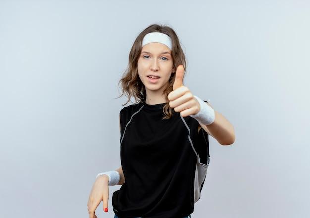Młoda dziewczyna fitness w czarnej odzieży sportowej z pałąkiem na głowę uśmiecha się pokazując kciuki stojąc na białej ścianie
