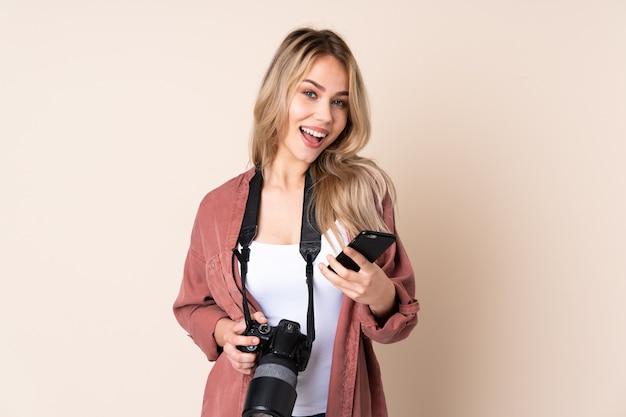 Młoda dziewczyna fotograf na pojedyncze ściany z telefonem w pozycji zwycięstwa
