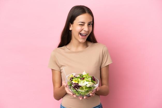 Młoda dziewczyna francuski na białym tle na różowym tle, trzymając miskę sałatki podczas mrugania