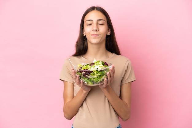Młoda dziewczyna francuski na białym tle na różowym tle, trzymając miskę sałatki z happy wypowiedzi