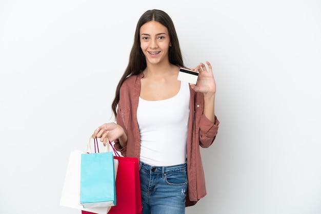 Młoda dziewczyna francuski na białym tle trzymając torby na zakupy i kartę kredytową