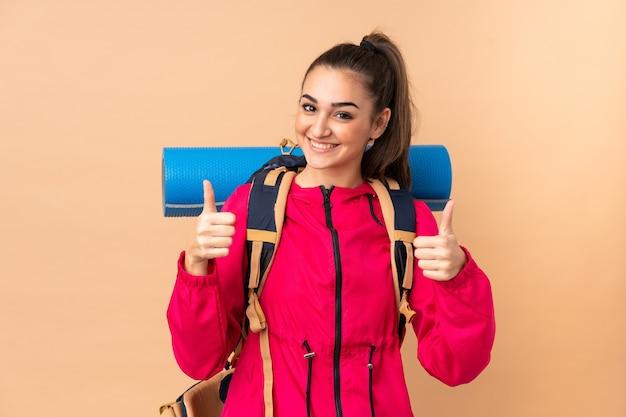 Młoda dziewczyna góral z dużym plecakiem na białym tle na beżowej ścianie, dając kciuk w górę gestu