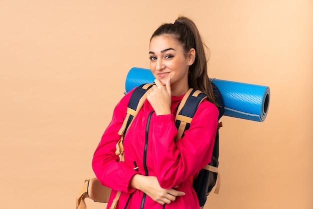 Młoda dziewczyna góral z dużym plecakiem na białym tle na beżowej ścianie śmiejąc się