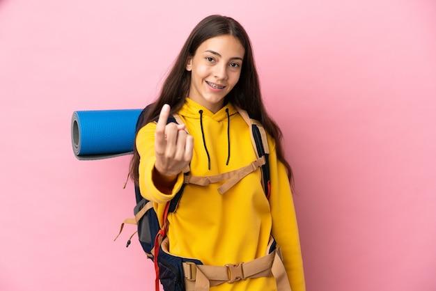 Młoda dziewczyna góral z dużym plecakiem na białym tle na różowym tle robi nadchodzący gest