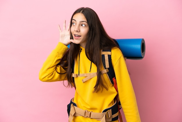 Młoda dziewczyna góral z dużym plecakiem na białym tle na różowym tle, słuchając czegoś, kładąc rękę na uchu