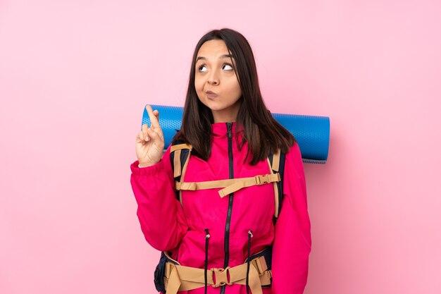 Młoda dziewczyna góral z dużym plecakiem na białym tle różowym z palcami krzyżującymi się i życząc wszystkiego najlepszego
