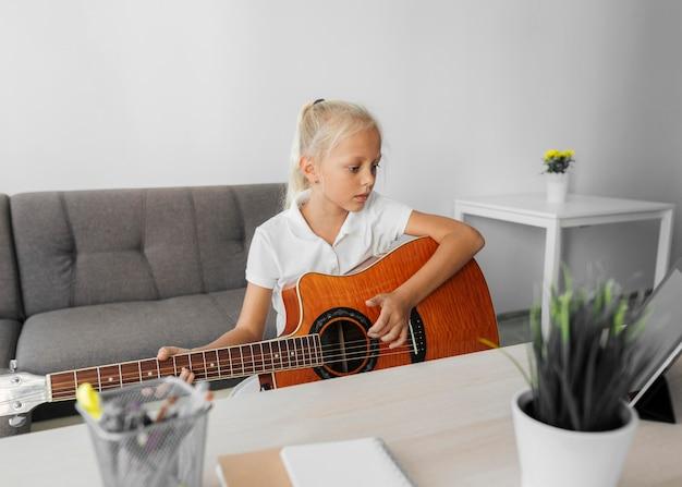 Młoda dziewczyna gra na gitarze w domu