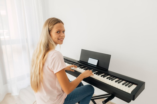 Młoda dziewczyna gra na instrumencie klawiszowym w domu