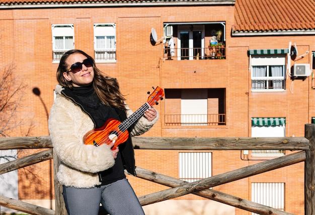 Młoda dziewczyna gra na ukulele w dzielnicy mieszkalnej z okularami przeciwsłonecznymi