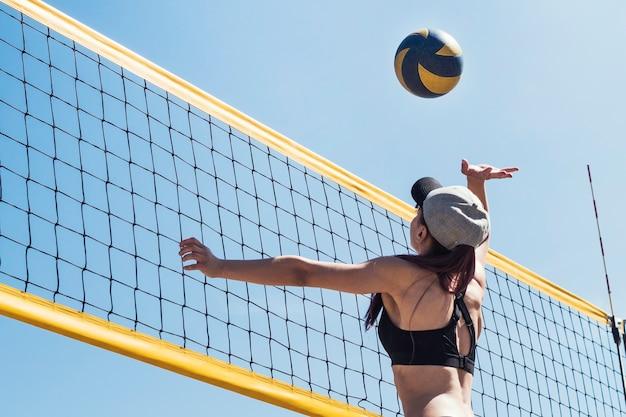 Młoda dziewczyna gra w siatkówkę plażową. gry sportowe. mecz siatkówki plażowej. zajęcia sportowe na świeżym powietrzu, czas zabawy na wakacjach.