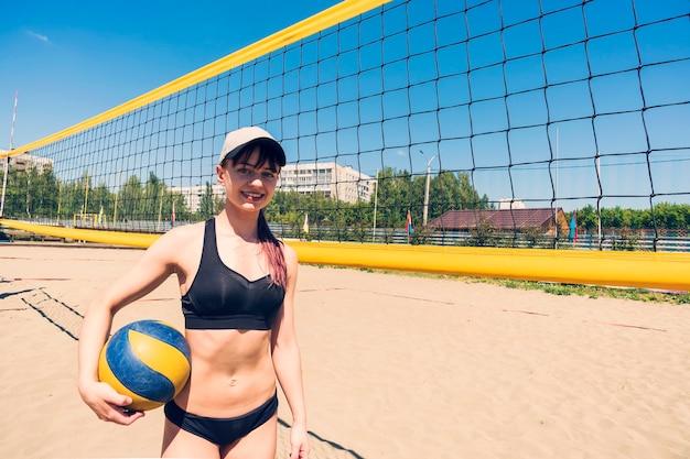 Młoda dziewczyna gra w siatkówkę plażową. mistrzostwa w siatkówce plażowej. gry sportowe na świeżym powietrzu. kobieta stoi z piłką do siatkówki przy siatce na plaży.