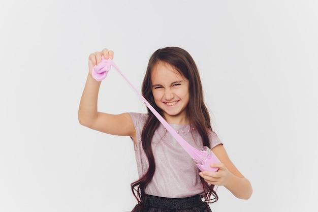 Młoda dziewczyna gra ze szlamem. pojedynczo na białym tle.