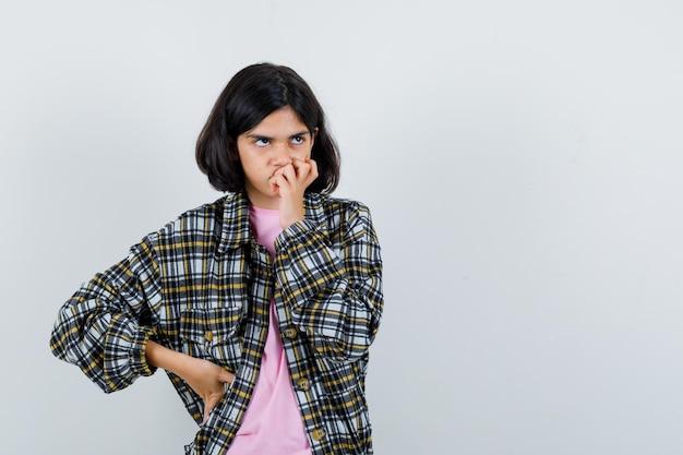 Młoda dziewczyna gryzie palce trzymając rękę w talii, myśląc o czymś w kraciastej koszuli i różowym t-shircie i patrząc zamyśloną