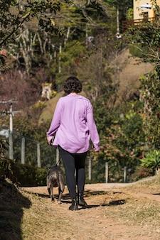 Młoda dziewczyna i jej pies pit bull spaceru na polnej drodze. ona i pitbull ćwiczą. słoneczny dzień.
