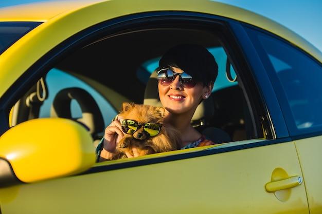 Młoda dziewczyna i pies w samochodzie na letnie podróże
