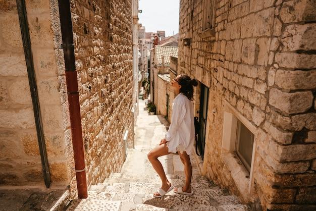 Młoda dziewczyna idąc przez starożytne wąskie uliczki w piękny letni dzień