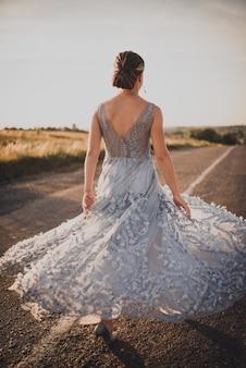 Młoda dziewczyna idzie asfaltową drogą w szarej niebieskiej długiej sukni o zachodzie słońca. plecy i ramiona otwarte