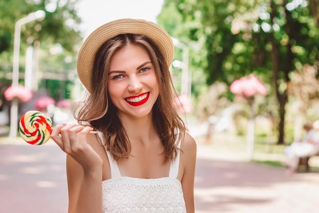 Młoda dziewczyna idzie do parku i uśmiecha się z okrągłym lizakiem w dłoni