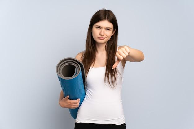 Młoda dziewczyna idzie na zajęcia jogi, trzymając matę pokazując kciuk w dół z negatywnym wyrazem twarzy