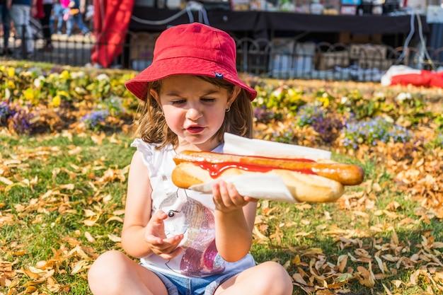 Młoda dziewczyna je hot dog. duża niemiecka kiełbasa w kok.