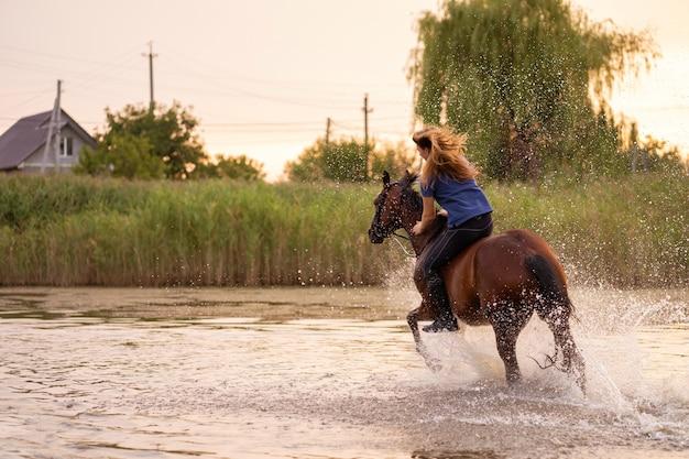 Młoda dziewczyna jedzie konia na płytkim jeziorze. koń biegnie po wodzie o zachodzie słońca. opiekuj się i chodź z koniem. siła i piękno