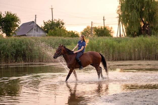 Młoda dziewczyna jedzie konia na płytkim jeziorze.