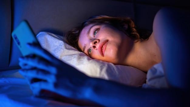 Młoda dziewczyna jest na swoim smartfonie w łóżku. niebieskie podświetlenie w pomieszczeniu
