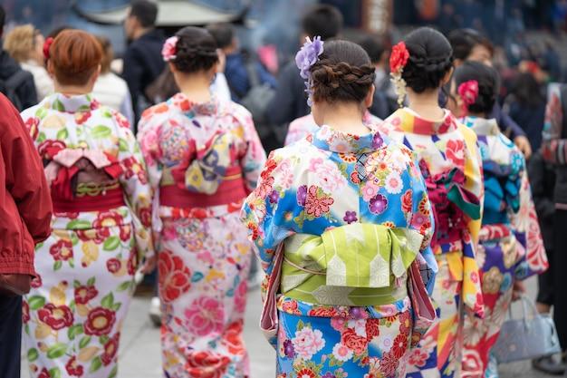 Młoda dziewczyna jest ubranym japońską kimonową pozycję przed sensoji świątynią w tokio, japonia.