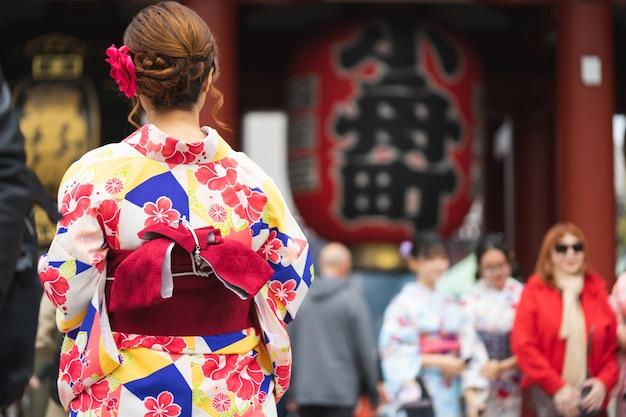 Młoda dziewczyna jest ubranym japońskiego kimono stoi przed sensoji świątynią w tokio