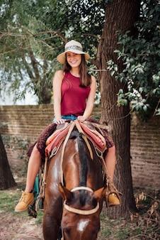 Młoda dziewczyna jest ubranym kapelusz i jedzie konia