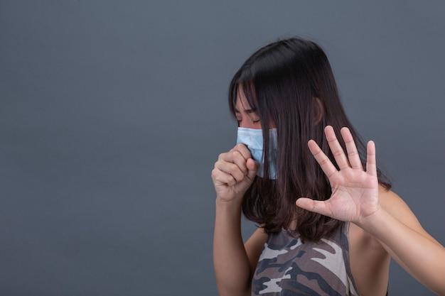 Młoda dziewczyna jest ubranym maskę podczas gdy kaszlący na czerni ścianie.
