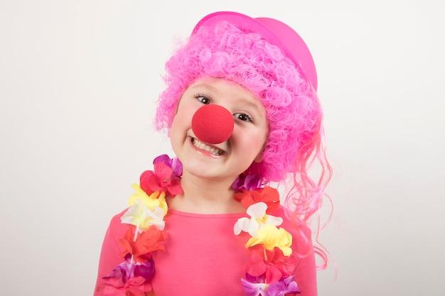 Młoda dziewczyna jest ubranym perukę i błazenu szkła i ono uśmiecha się dla karnawału