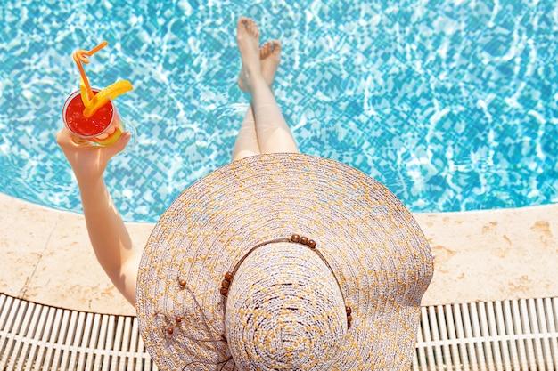 Młoda dziewczyna jest ubranym słońce kapelusz jest usytuowanym basenem przy koktajlem