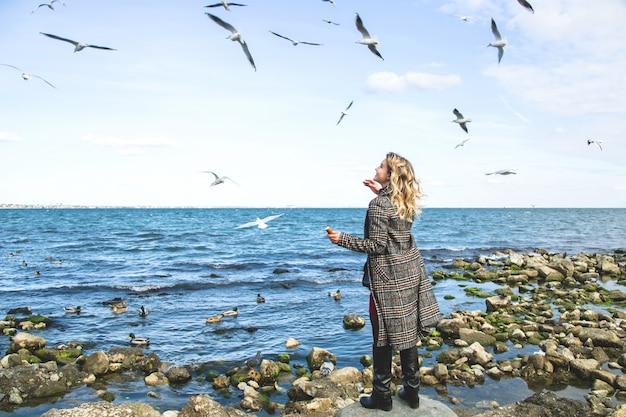 Młoda dziewczyna karmi mewy stojące na brzegu morza.