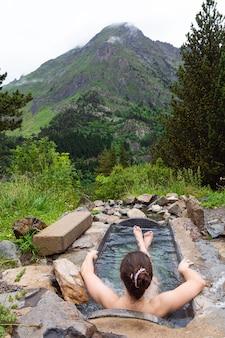 Młoda dziewczyna kaukaska kąpie się w łaźni termalnej w zimny i pochmurny dzień w benasque, huesca, hiszpania