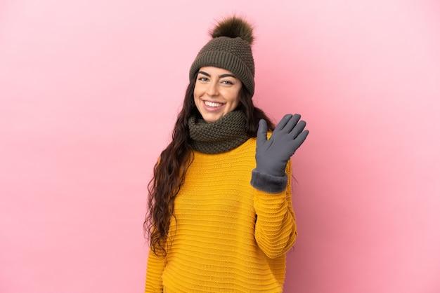 Młoda dziewczyna kaukaska z czapką zimową na białym tle na fioletowym tle salutowania ręką z happy wypowiedzi