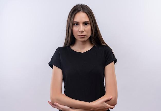 Młoda dziewczyna kaukaski na sobie czarną koszulkę skrzyżowaniu rąk na na białym tle białej ścianie